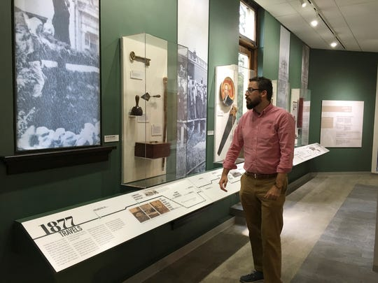 Kevin Moore, associate curator of artifacts, shows