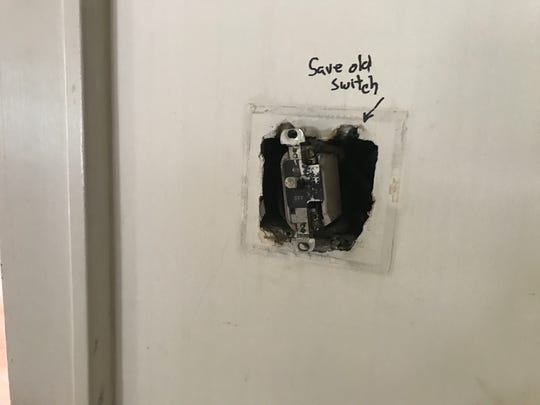 Robert Williams, president of the Verona Historical Society, has marked an old lightswitch in his home to be saved while the residence is renovated, following a fire earlier this year.