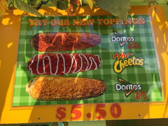 A sign at the Corn Roasters West booth alerts Ventura County Fair attendees to new toppings made from crushed Cheetos and corn chips.