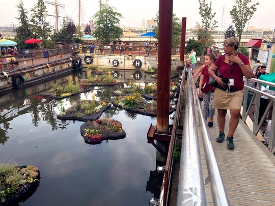 Janlynn Miller and her daughter Savannah Richards, advisors, look at a pond created by 3 barges at Spruce Street Harbor Park in Philadelphia on the Delaware riverfront on Thursday, July 19, 2017.