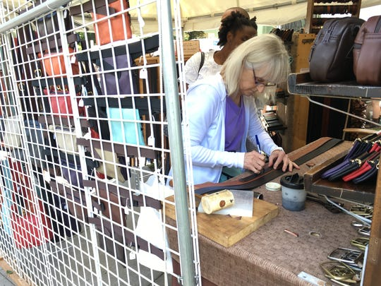 Sandy Dalrymple makes marks on a customer's leather belt in her tent at Park Ave Fest. Her husband, Conrad, has participated in the festival since its inaugural year in 1976.