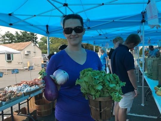 Tara Merry, 40, of Nutley, shows off her finds at a farmers market in Nutley on Sunday, Aug. 6, 2017.