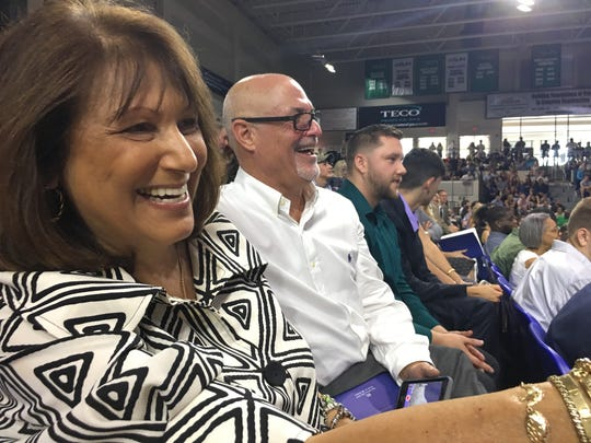 """""""She's hugging everyone,"""" Debbe Schertzer says pointing to daughter Courtney Faunce and laughing with husband Danny Schertzer as Faunce hugs each faculty and staff member standing to greet master's degree recipients after they leave the stage Saturday, Aug. 5, 2017 in Alico Arena."""