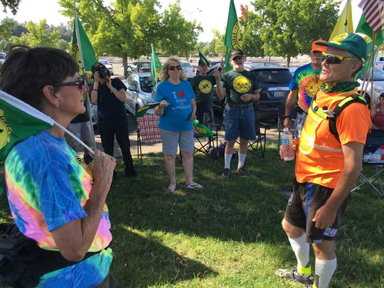 State of Jefferson supporter Jan Hanks of Shasta, left, greets runner Hervé Leconte after he arrives Saturday in Redding.