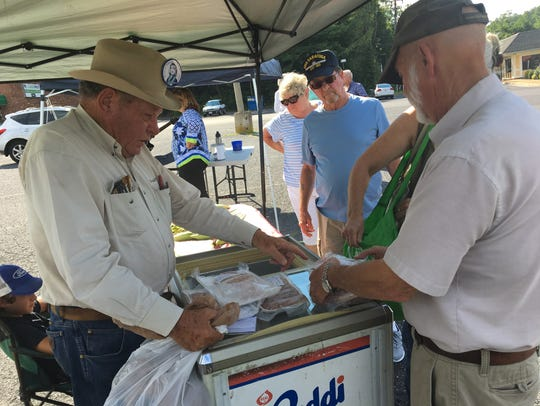 Frank Nolen hands out sausage to customers at a new