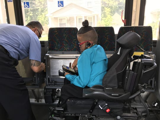Jensen Caraballo (right) is secured to the Q'POD wheelchair passenger station on an RTS bus.