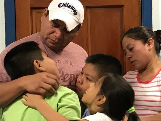 Jose Estrada Lopez of Fairview hugs his children days