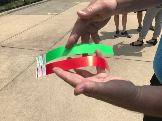 Jeff Scheibel, president and CEO of the YMCA of Metropolitan Lansing, shows the red and green wristbands July 26, 2017. The green bands are for those who pass a swim test.