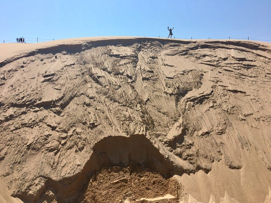 Photographer Andraya Croft is pictured after hiking atop the sand dune that threatens the Dresslers' summer home July 31, 2017 at Silver Lake.
