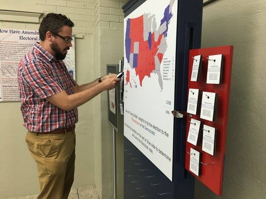Kevin Moore, associate curator of artifacts at the Rutherford B. Hayes Presidential Library & Museums, shows how the Electoral College works on the museum's interactive display.