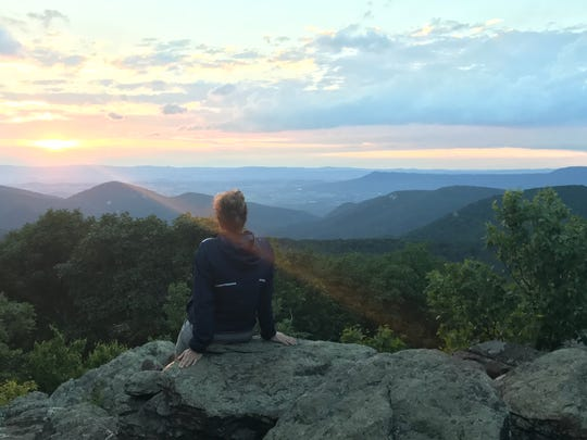 Jan Williams watches the sunset on Loft Mountain while taking a break from hiking the Appalachian Trail.
