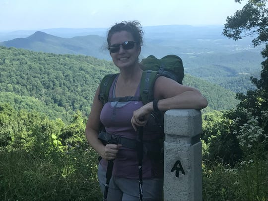 Jan Williams standing at the trail maker located at the Ivy Creek overlook on the Appalachian Trail.