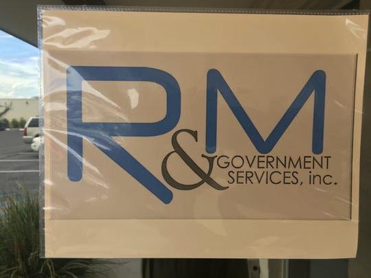 R & M Government Services logo hangs inside the door to their Las Cruces office.