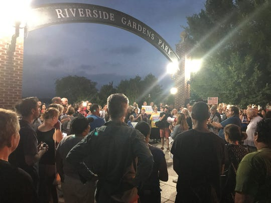 A couple hundred people gather at Riverside Gardens