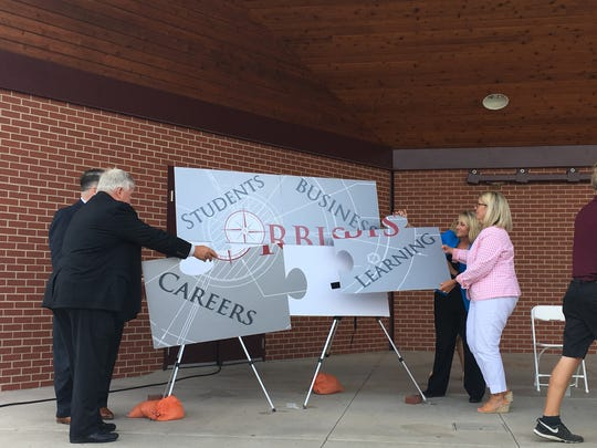 """Ankeny community leaders put together a puzzle spelling, """"Orbis,"""" during the program's name unveiling at the Ankeny Band Shell on Aug. 10."""