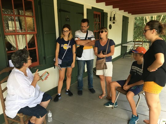 Becca Begnaud speaks with a French family about traiteurs, faith healers, at Acadian Culture Day at Vermilionville Sunday, Aug. 13. Amandine, Eric, Sandrine, Arnaud and Amelie Jeunot are visiting from Lyon, France.