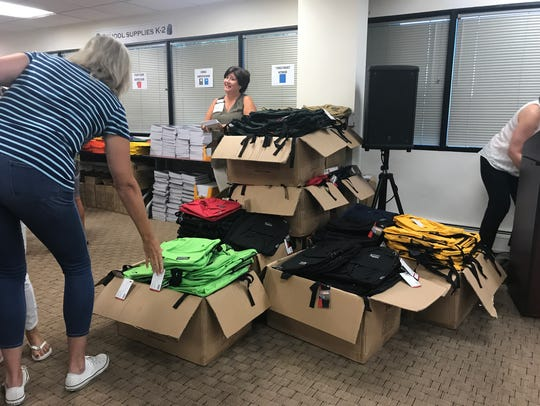 Volunteers grab new backpacks, which they then filled