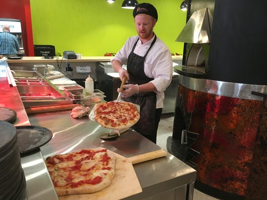 Zach Beckman of Fremont makes pizza at Elroy's Deli Market in downtown Fremont.