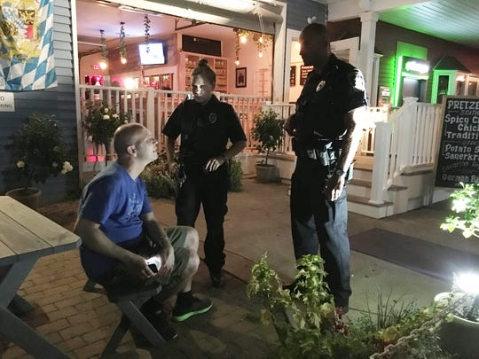 Put-in-Bay police officers question a tourist at the Biergarten bar after he fell asleep at a table on Saturday, August 12. The man, who said it was his anniversary, was allowed to leave after his wife came to get him.