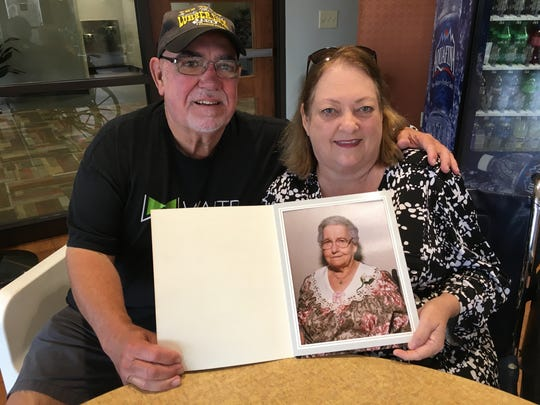 Dan and Sandra Gaspard hold a photo of Ednes Gaspard, who was a traiteur, or faith healer, in the Maurice community.