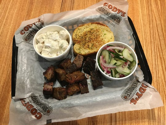 A plate of burnt ends, garlic bread, potato salad and