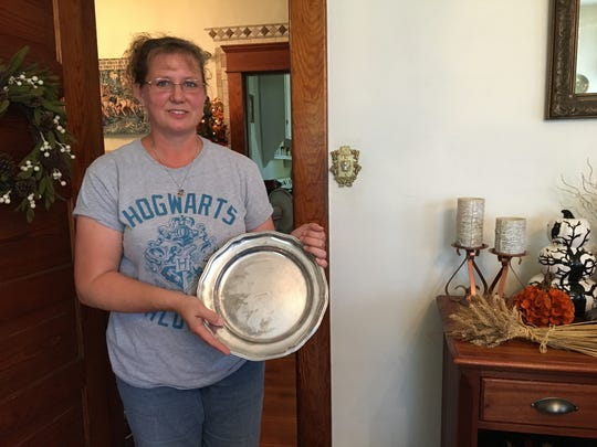Mia Pugh holds one of her pewter plates while standing