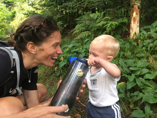 Jennifer Pharr Davis stops for a water break on the trail with her son, Gus, whom she is carrying for most of the hike across the state.