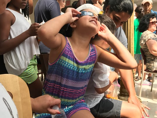 Mila Lelinho, 5, of Belleville views the solar eclipse