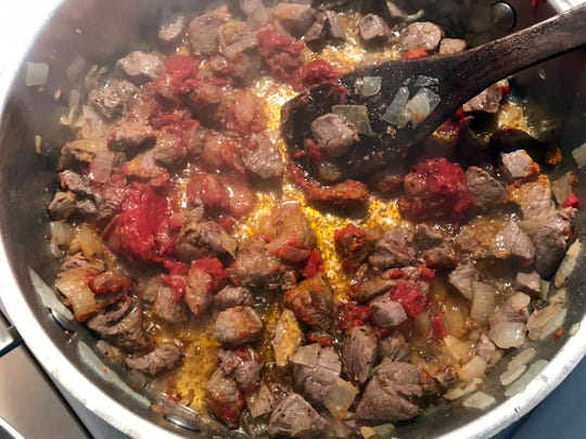 Fry the tomato paste and turmeric to color the oil before adding water