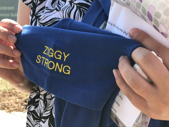 "Heather Zyszkiewicz Sharafinski holds up a new uniform option for Department of Neighborhood Service workers that honors her father, Greg ""Ziggy"" Zyszkiewicz."