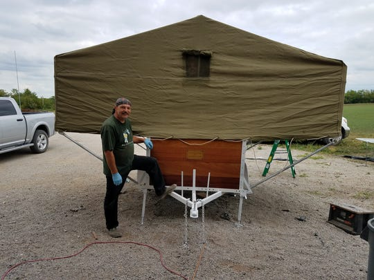 A picture of the popup camper after it was completed. The picture shows the small window in the canvas topper. Daniel Hilgers, Teagan's grandfather, poses with the camper.