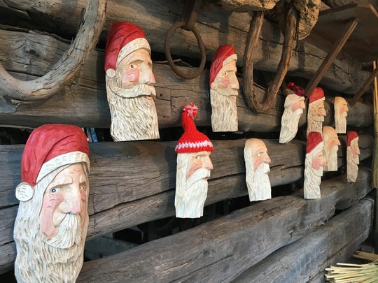 Santa Claus carvings made by Don Leiser of Oak Harbor are displayed at the Sandusky County Fair on Wednesday.