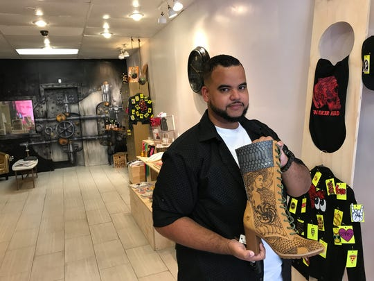 Kelvis Polanco, owner of Play Money Goods, shows off a custom-designed boot on Aug. 23, 2017, at Bloomfield Center.