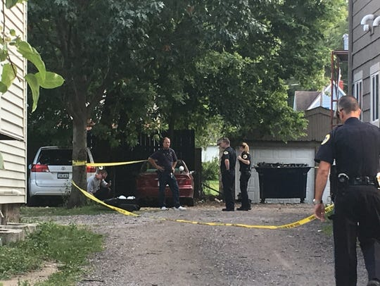 Police investigate the backyard and driveway of 1439