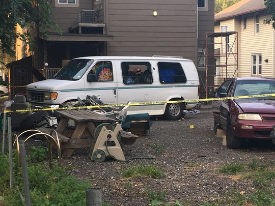Police investigate the backyard and driveway of 1439 Henderson Avenue. A person was set on fire near the home and critically injured, according to police.