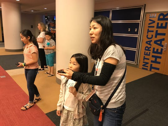 A mother and daughter try out a drone at Liberty Science