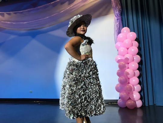 Chelsea Ogo flaunts her costume made of recycled newspapers