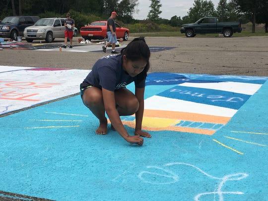 Jenna Radomski, 17, writes letters in chalk before
