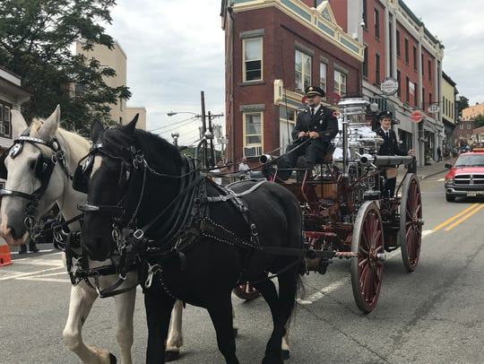 Horses pull a fire pumper in the annual Boonton fireman's