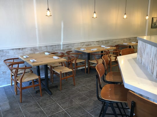 Seating options at Moody Rooster in Thousand Oaks include tables and wishbone chairs, left, and a dining counter that looks into the open kitchen.