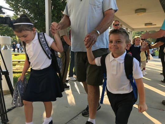 Two students are walked into Carter G. Woodson Elementary
