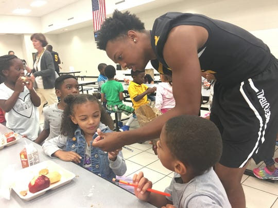 Central Gwinnett High quarterback and Kentucky Wildcats commitment Jarren Williams hands out pencils during lunch to Jenkins Elementary School students in Lawrenceville, Georgia on Tuesday, August 29, 2017.