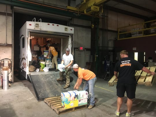Volunteers load supplies onto pallets for distribution.