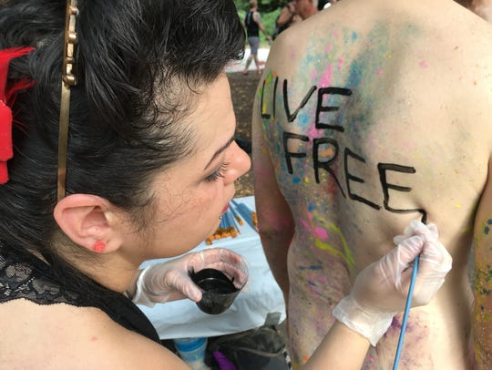 Artist Nicole Tossas paints a slogan on the back of