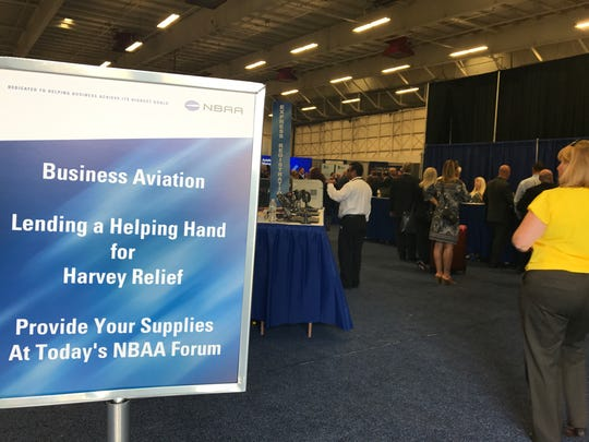 Attendees pass a Hurricane Harvey relief  sign at the National Business Aviation Association regional forum Sept. 7, 2017, at Morristown Municipal Airport in Hanover, N.J.