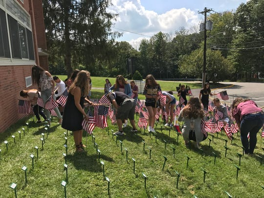 Cedar Grove High School students place flags, in memory