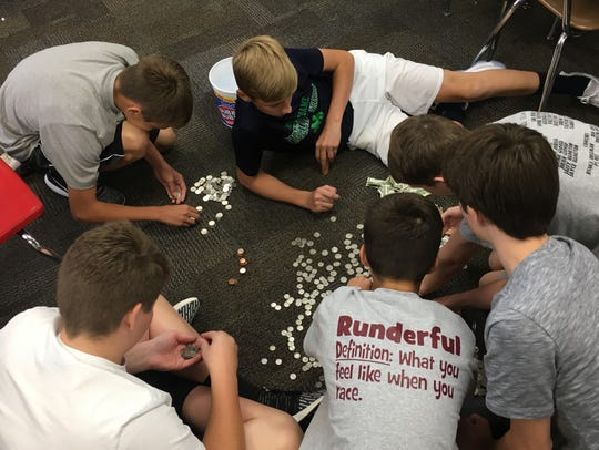 Mount Vernon eighth grade students count money for
