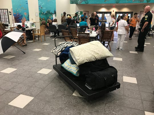 Volunteers at the Manatee Elementary School hurricane shelter in Viera help evacuees move their belongings into classrooms before Hurricane Irma in 2017.
