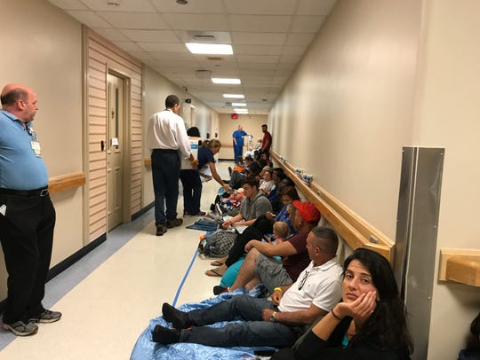 Hurricane Irma evacuees shelter in a hallway Sunday,
