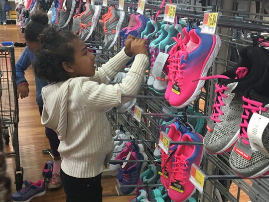 Six-year-old Nevaeh Boals looks for her size in the